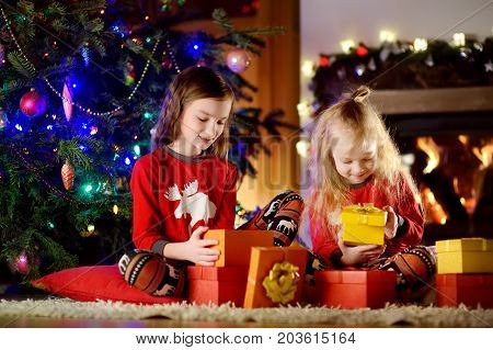 Happy Little Sisters Wearing Christmas Pyjamas Playing By A Fireplace In A Cozy Dark Living Room On
