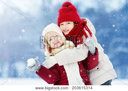 Two Adorable Little Girls Having Fun Together In Beautiful Winter Park. Beautiful Sisters Playing In