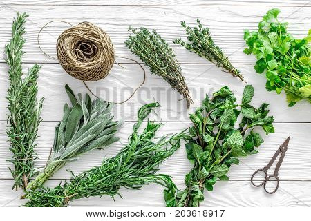 drying fresh herbs and greenery for spice home food on white wooden kitchen desk background top view pattern