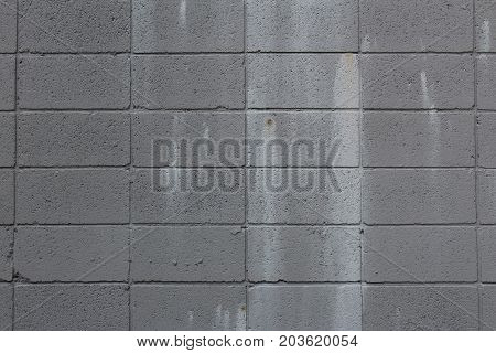 Grey cinder block wall with paint stains, horizontal aspect