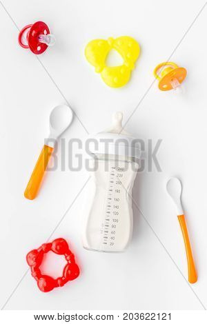 bottle with breastmilk and infant formula powdered healthy food, spoons and bib on white desk background top view