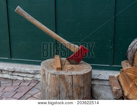 Red Axe In Log next to wood pile for indoor fireplace