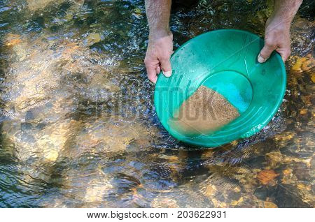 Gold pan filled with mineral rich material.  Prospecting for gold and gemstones. Fun and adventure enjoying the recreational  outdoor activity of panning for gold.
