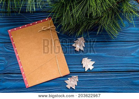 toys to decorate christmas tree for new year celebration with fur tree branches and notebook on blue wooden table background top veiw mockup