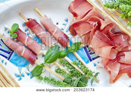 Plate With Prosciutto Breadsticks And Basil