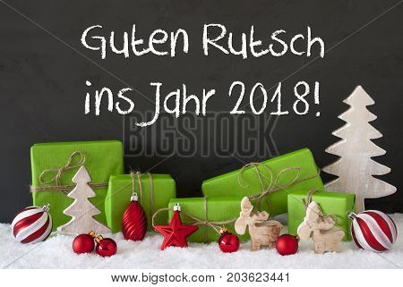 German Text Guten Rutsch Ins Jahr 2018 Means Happy New Year 2017. Green Gifts With Christmas Decoration Like Tree, Moose Or Red Christmas Tree Ball. Black Cement Wall As Background With Snow.
