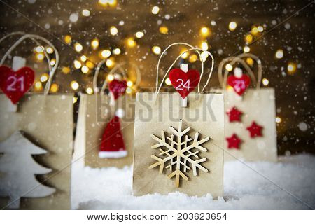 Christmas Shopping Bag With Numbers 21 to 24 On Snow. Decoration Like Santa Hat, Snowflake, Christmas Tree And Stars. Fairy Lights In Background. Snowy Scenery With Snowflakes