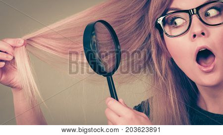 Haircare problems concept. Shocked blonde woman holding magnifying glass investigating her hair.