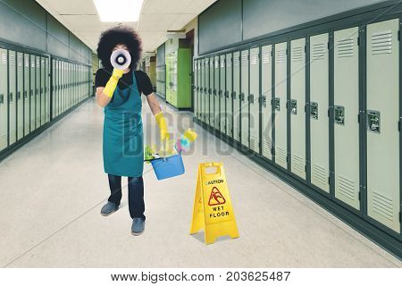 Male janitor is speaking with a megaphone while holding a bucket and standing near a wet floor sign in the school corridor