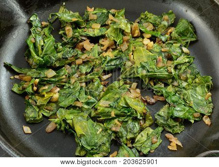 Close up of sauteed collard greens with chopped shallot in cast iron frying pan skillet