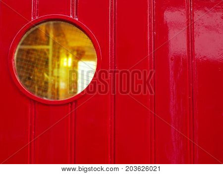 red wood pattern wall of house or ship with circle glass orange light window background