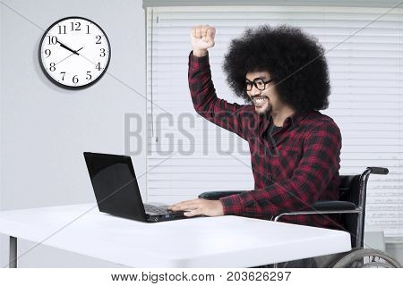 Disabled man sitting on a wheelchair and working with laptop while raising hand in the workplace