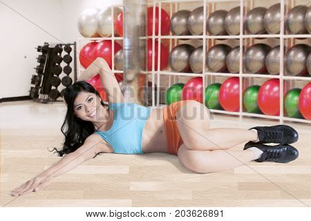 Photo of a beautiful woman looking at the camera while doing a workout in the fitness center