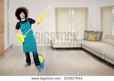 Picture of an Afro maid is playing guitar with a broom while standing in the living room