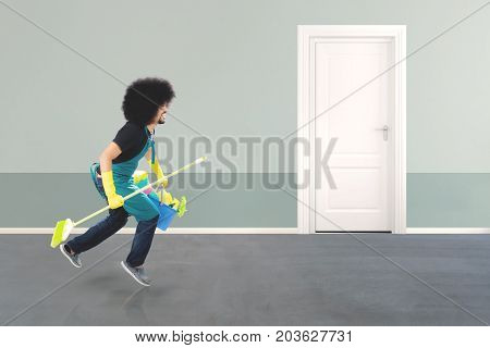 Side view of an Afro male janitor running in the hotel corridor while holding a broom and bucket