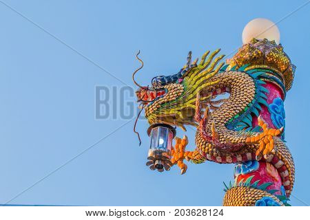 chinese dragon statue with lamb on the pole.