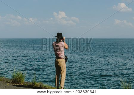 Republic of Armenia. Photographer holds a camera and photographs the lake Sevan.