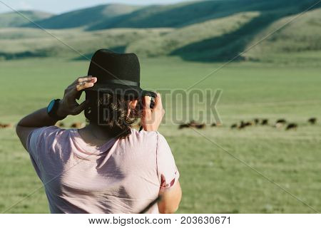 Photographer holds a camera and photographs. Back view.
