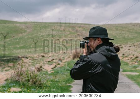 Photographer holds a camera and photographs. Side view.
