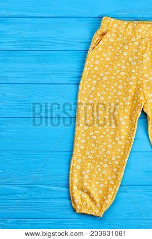 Baby girl pants on wooden background. Yellow cotton baby girl trousers in floral print, blue wooden background.