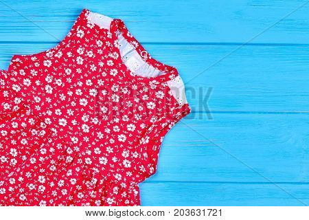 Baby child girl red fancy dress. Cotton baby-girl dress in vintage print on blue wooden background. Natural dress for kids on sale.
