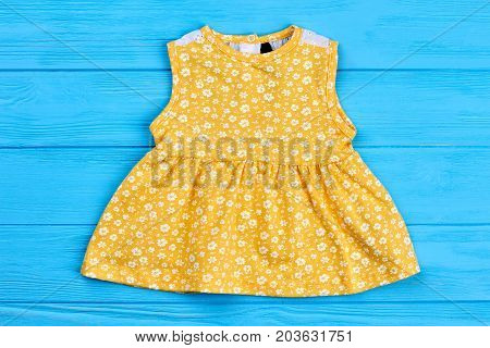 Yellow cotton dress for newborn. Sleeveless sundress for infant girl on blue wooden background. Casual dress in vintage print for baby-girl.
