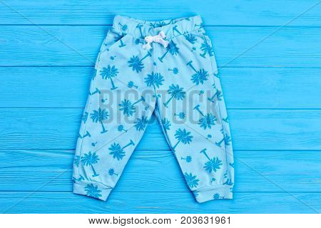 Light blue palm print baby pants. Blue patterned baby trousers on blue wooden background. Natural kids apparel.
