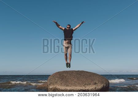 Strong man posing on a stone against a background of a bay and the sky. Photo in the daytime. poster