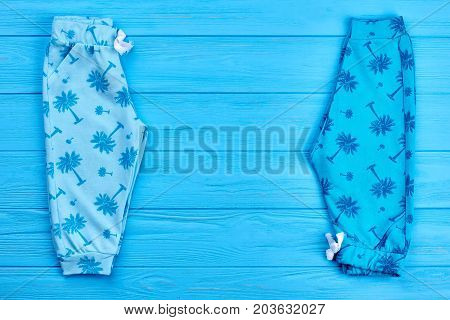 Baby summer pants and copy space. Blue printed high quality infant baby trousers on blue wooden background. Dainty design baby summer outfit.