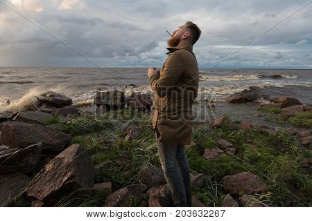 Bearded Man with a cigarette on the seashore in stormy weather