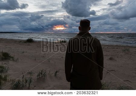 Brutal man looking at the sunset by the sea