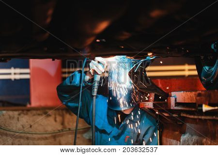Man in a mask does welding machines.