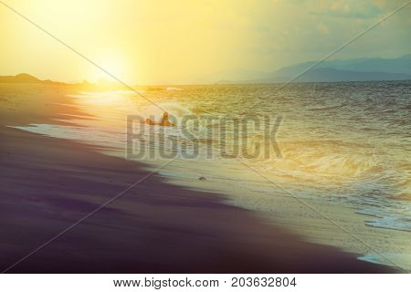 silhouette of happy men in the sea of dark beach at sunset soft tone like dream