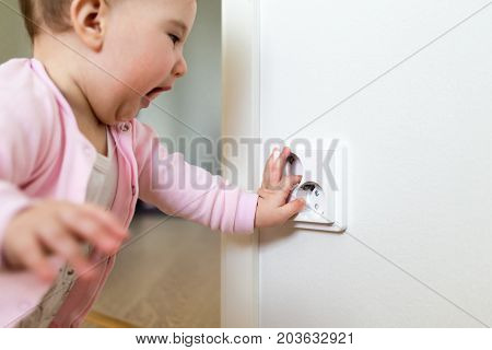 Small child touches an electrical outlet at home. Safety of children.