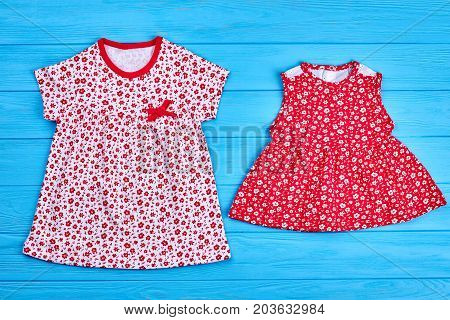 Kids summer cotton clothes. Little girl natural cotton gowns. Set of childs summer dresses on blue wooden background.
