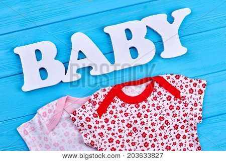 Set of patterned baby-girl clothing. New cotton garment for newborn baby, blue wooden background. Shop natural baby clothes, figure baby.