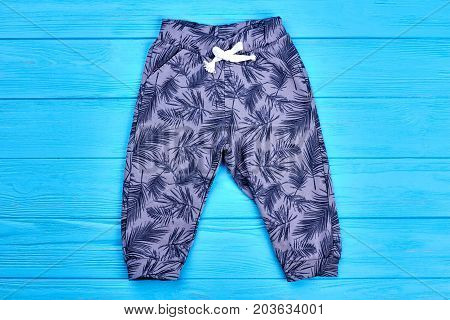 Baby-girl new patterned cotton leggings. Purple printed pants for toddlers on blue wooden background. High quality cotton clothes for kids.