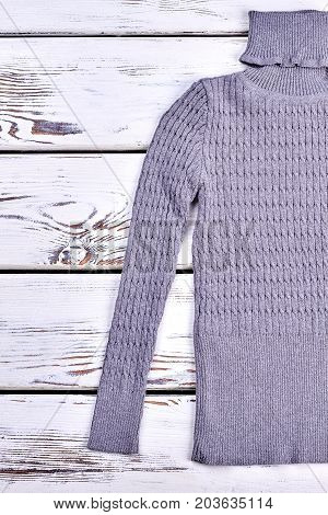 Gray turtleneck texture design sweater. Gray turtle neck sweater on old white background. Warm clothes for kids on sale.