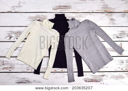 Set of turtleneck knitted sweaters. Collection of new colored thick turtleneck sweaters for children, top view.