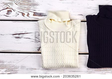 Black and white turtleneck sweaters. New folded knitted sweaters for childrens, old wooden background.