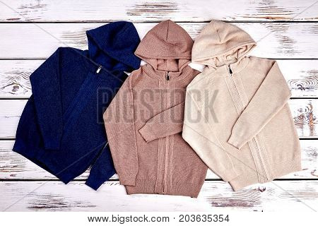 Collection of new knitted hooded sweaters. Set of cute hooded knit cardigans on old wooden background. High quality cotton pullovers.