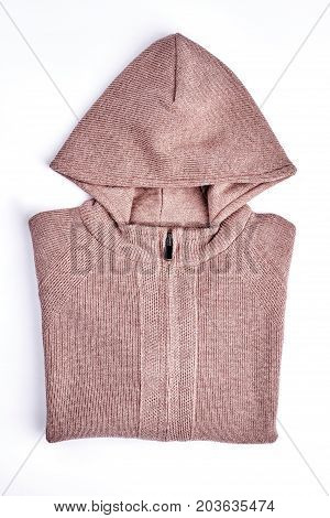 New hooded pullover for children. Knitted brown jacket with hoodie folded on white background. Children trendy warm apparel on sale.