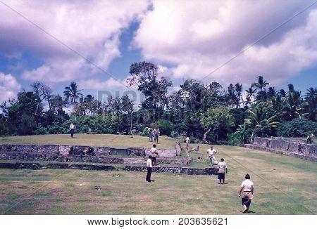 MU'A, TONGATAPU / TONGA - CIRCA 1990: Visitors explore and climb upon the ancient burial mounds near Mu'a.