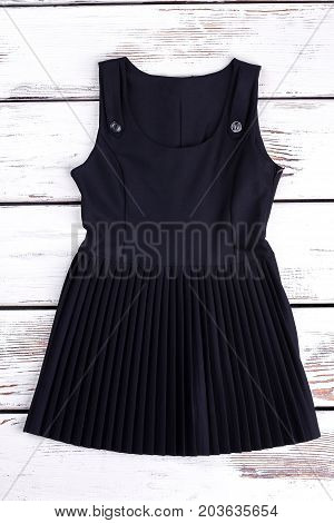 Girls black cotton dress with folds. Black cotton knee-length pleats classic dress for girls isolated on old vintage background. Little girls pleated jumpers.
