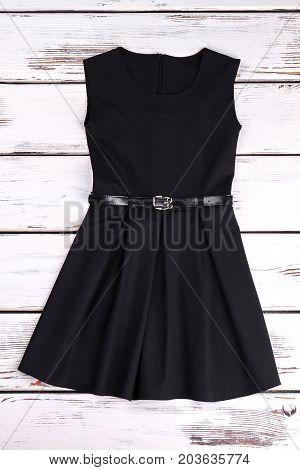 Girls elegent black cotton dress. A-line short black dress with belt for little girls, old wooden background.