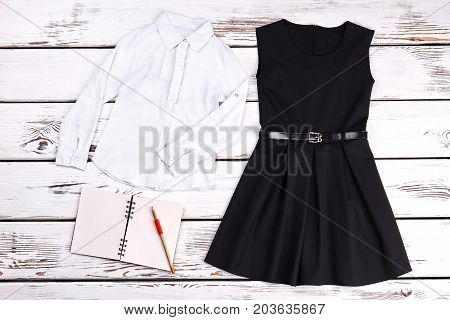 Girls school clothes and accessories. White girls shirt, black dress, notebook, pensil on old wooden background. Childrens school apparel and accessories.