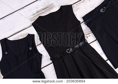 Black school apparel for girls. Girls school belted skater dress, skirt, old wooden background.
