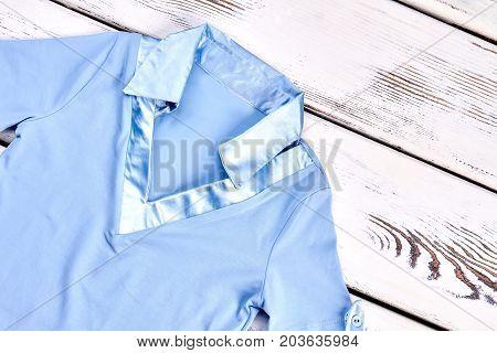 Girls elegant blue blouse for school. Beautiful girls shirt with silk collar on wooden background. Girls modern garment for school wear.