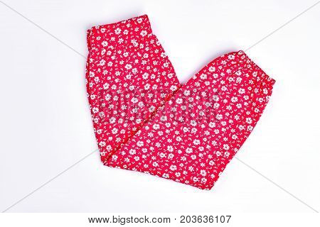 Baby-girl red cotton pants. Toddler girls new folded trousers with a pattern of small white flowers, isolated on white background.