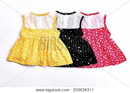 Infant girl cute design sundresses. Collection of beautiful patterned drsses with embroidery for baby-girls, white background. Infant girls casual summer outfit.